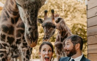 couple posing with giraffe